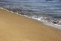 Gold sand and sea foam Stock Photo