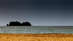 Gold sand with silhouette island and dark sky. Gold sand on beach with sea, silhouette island and dark sky Royalty Free Stock Images