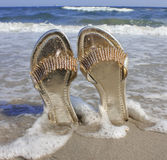 Gold sandals on a ocean beach Stock Photography