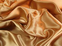 Gold satin. A loosely laid sheet of gold satin royalty free stock image