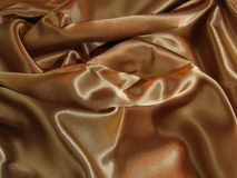 Gold satin. A loosely laid sheet of gold satin royalty free stock photography
