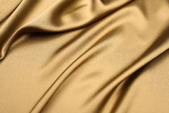 Gold satin background. Silky smooth and soft gold satin cloth background with nice foldings Stock Photo