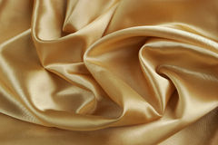 Gold Satin Background - Horizontal. Lustrous folds of gold satin fabric symbolizing luxury, elegance, and sensuality Stock Images