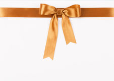 Gold satin ribbon with a bow Royalty Free Stock Images
