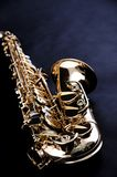 Gold Saxophone Isolated on Black Bk. A Saxophone isolated against a low key black background in the vertical view Stock Photos