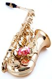 Gold Saxophone Pink Rose. A gold saxophone with a pink rose isolated on a high key white background in the vertical view Royalty Free Stock Photos