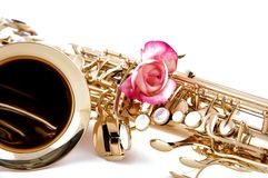 Gold Saxophone And Pink Rose on White Bk. A gold saxophone with a pink rose isolated against a white high key background in the horizontal view Royalty Free Stock Photography