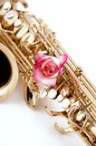 Gold Saxophone And Pink Rose on White Bk. A gold saxophone with a pink rose isolated against a white high key background in the vertical view Royalty Free Stock Photography
