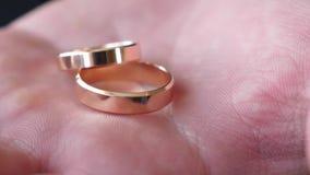 Gold schellt ein Geschenk für die geliebte Frau auf der Palme des Mannes Nahaufnahme Bräutigam hält in seinem Handkasten Goldhoch stock video