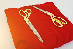 Gold scissors on a red silk cushion for grand opening Stock Images