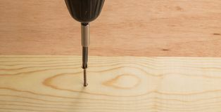 Gold screw being measured and driven into a board Royalty Free Stock Images
