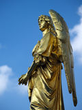 Gold sculpture of an angel. In a cloudy sky Royalty Free Stock Photos