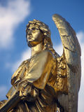 Gold sculpture of an angel. In a cloudy sky Stock Photos