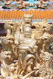 Gold sculpture of deity in the Chinese temple. Royalty Free Stock Photography