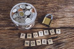 Gold security lock and full coins with jar, Words PROTECT MONEY. Made block wooden letters. Wood abc. Save Money Concept used for financial protection royalty free stock photography