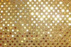 Gold sequins on Metallic fabric fashion background / pattern Stock Image
