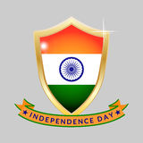 Gold shield with the flag of India and Independence Day inscription on a gray background. Stock Images