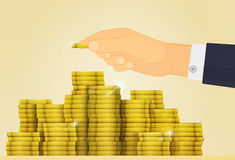 Gold shine treasure. Lottery Jackpot or money in Bank. Hand adds a coin to the other coins Royalty Free Stock Image