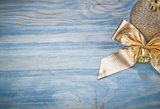 Gold-shining Christmas ball bow on wooden board celebrations con Royalty Free Stock Image