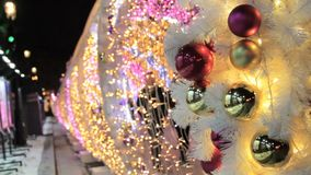 Gold shiny balls and garland on white fir tree. Happy New Year and Xmas theme. Alley with blurred shimmering garland. Lights, holidays background. People walk stock video