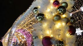 Gold shiny balls and garland on white fir tree. Happy New Year and Xmas theme. Alley with blurred shimmering garland. Lights, holidays background. People walk stock footage