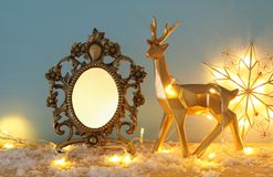 Gold shiny reindeer and empty photo frame on snowy wooden table with christmas garland lights. For photography and scrapbook monta Royalty Free Stock Photos