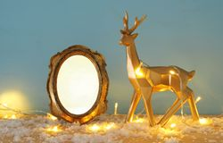Gold shiny reindeer and empty photo frame on snowy wooden table with christmas garland lights. For photography and scrapbook monta. Ge royalty free stock photo