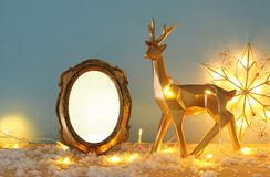 Gold shiny reindeer and empty photo frame on snowy wooden table with christmas garland lights. For photography and scrapbook monta. Ge royalty free stock images