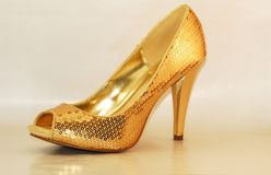 Gold shoe. Isolated gold sequined high heel shoe Stock Photos