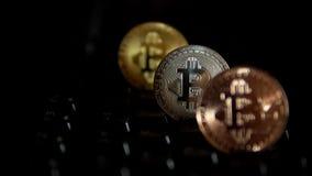 Gold, Silber, Bronze, bitcoin prägt auf dem Hintergrund einer blinkenden Tastatur stock footage