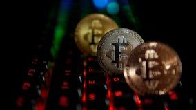 Gold, Silber, Bronze, bitcoin prägt auf dem Hintergrund einer blinkenden Tastatur stock video