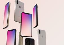 Gold-, Silber und Raum IPhone XS graue Smartphones, schwimmend in einer Luft, bunter Schirm stockfoto