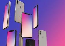 Gold-, Silber und Raum IPhone XS graue Smartphones, schwimmend in einer Luft, bunter Schirm lizenzfreie stockfotos