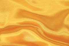 Gold silk. Smooth elegant gold silk fabric Royalty Free Stock Photo