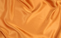 Gold silk. Y material with soft creases Royalty Free Stock Images