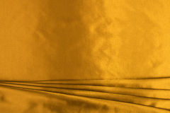 Gold silk. Background, texture, color richness, glamour stock images