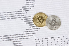 Gold and silver bitcoin on the background of binary code. Electronic money and cryptocurrency stock image