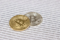 Gold and silver bitcoin on the background of binary code. Electronic money and cryptocurrency stock photo