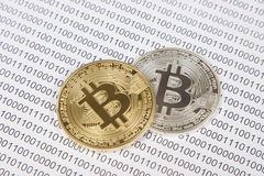 Gold and silver bitcoin on the background of binary code. Electronic money and cryptocurrency stock photos