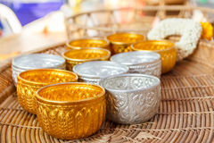 Gold and silver bowl on wooden basket. Stock Photo