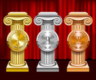 Gold, silver and bronze ancient columns and round medals with la Stock Images