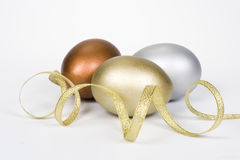 Gold, silver and bronze eggs. With gold tape. Isolated on a white background royalty free stock photos