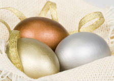 Gold, silver and bronze eggs Stock Image