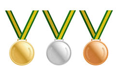 Gold, silver and bronze medals on green ribbons with shiny metallic surfaces. Gold, silver and bronze medals on green ribbons with shiny metallic surfaces Royalty Free Stock Image