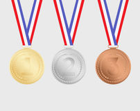Gold, silver and bronze medals with ribbons isolated on background. Royalty Free Stock Images