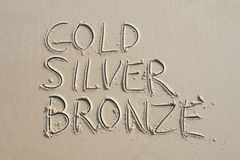Gold Silver Bronze Message on Smooth Sand Royalty Free Stock Photography