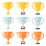 Gold, silver, bronze trophy in flat icons set. Royalty Free Stock Image
