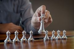 Gold and silver chess with player, Intelligent businessman playing chess game competition to planning business strategic to stock photos