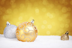 Gold and silver Christmas baubles on snow, gold background Royalty Free Stock Image