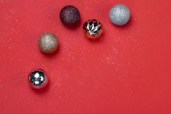 Gold and Silver Christmas ornament balls on red paper background. Gold and Silver Christmas ornament balls with carborundum on red paper background royalty free stock image